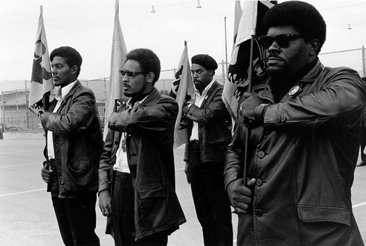 Four men stand and hold Panther flags. Foto: Pirkle Jones y Ruth-Marion Baruch